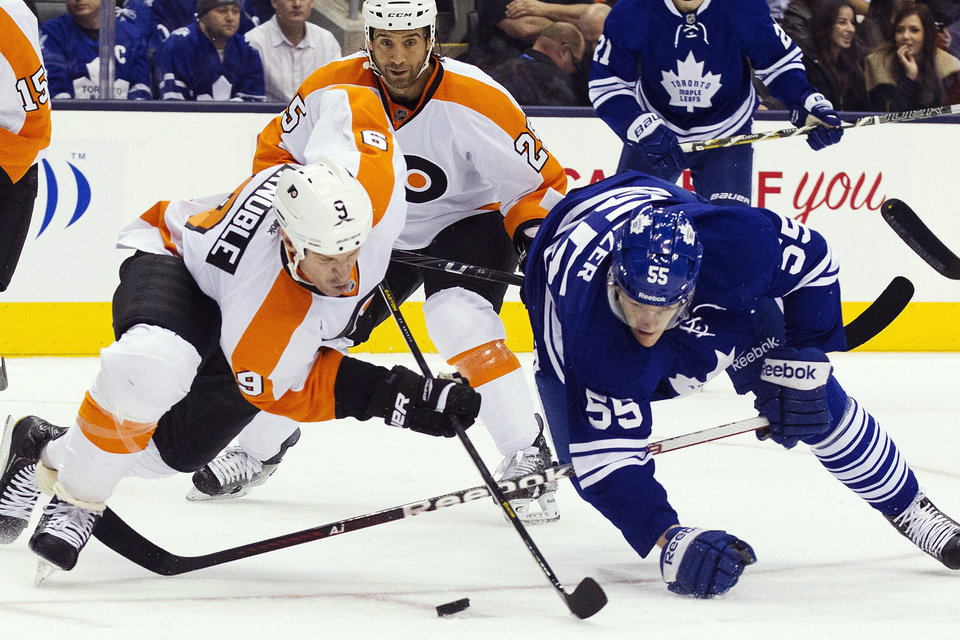 Toronto Maple Leafs\' Korbinian Holzer (55) and Philadelphia Flyers\' Mike Knuble (9) battle for the puck as Flyers\' Maxime Talbot watches during the first period of their NHL hockey game, Monday, Feb. 11, 2013, in Toronto. (AP Photo/The Canadian Press, Chris Young)