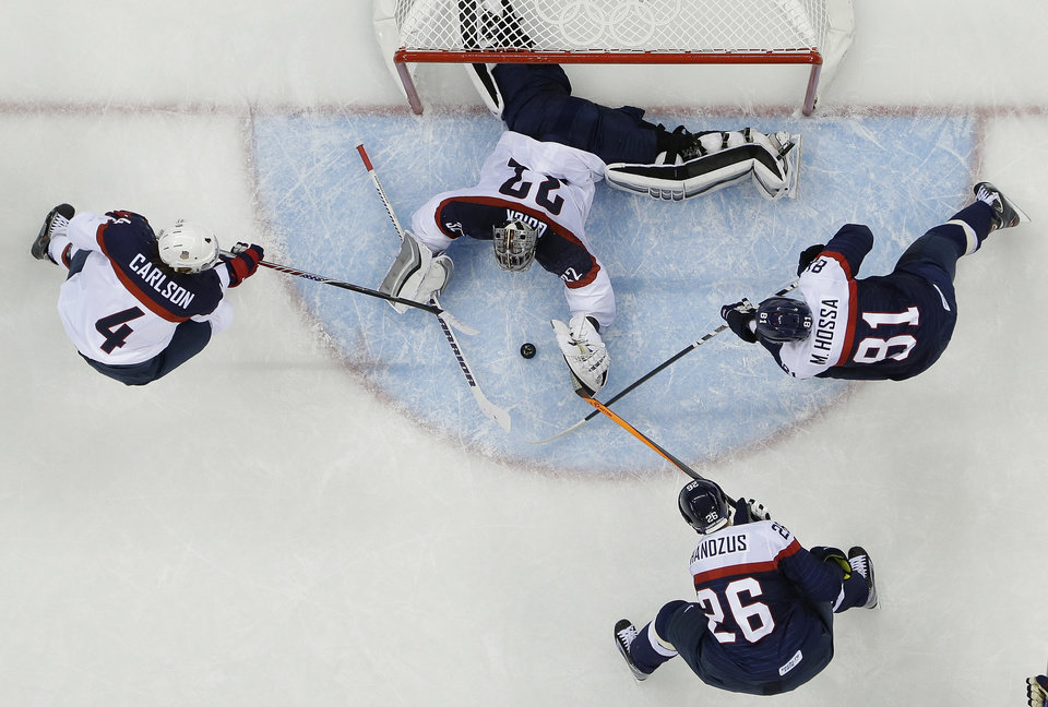 Photo - USA goaltender Jonathan Quick (32) reaches for Slovakia forward Michal Handzus's (26) shot at the goal as Slovakia forward Marian Hossa (81) adds pressure to the play and USA defenseman John Carlson (4) helps defend the goal during the 2014 Winter Olympics men's ice hockey game at Shayba Arena, Thursday, Feb. 13, 2014, in Sochi, Russia. USA defeated Slovakia 7-1. (AP Photo/Matt Slocum)