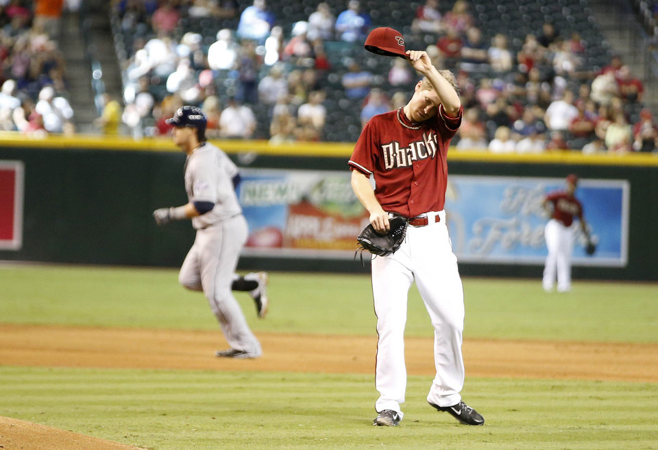 Photo - San Diego Padres' Yasmani Grandal rounds the bases as Arizona Diamondbacks' pitcher Chase Anderson wipes his brow after giving up the three run home run to Grandal in the fifth inning during a baseball game, Sunday, Aug. 24, 2014, in Phoenix. (AP Photo/Darryl Webb)