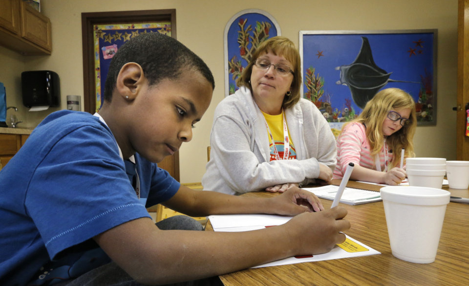 Photo -  Leader Ellen Spires works with Michael David and Casey Graves as kids attend Camp Noah on Thursday in Moore. Photo by Steve Sisney, The Oklahoman   STEVE SISNEY -  THE OKLAHOMAN