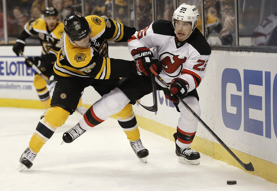 Photo - New Jersey Devils' Rostislav Olesz (25), of the Czech Republic, looks to pass off under pressure from Boston Bruins' Johnny Boychuk during the first period of an NHL hockey game in Boston, Saturday, Oct. 26, 2013. (AP Photo/Winslow Townson)