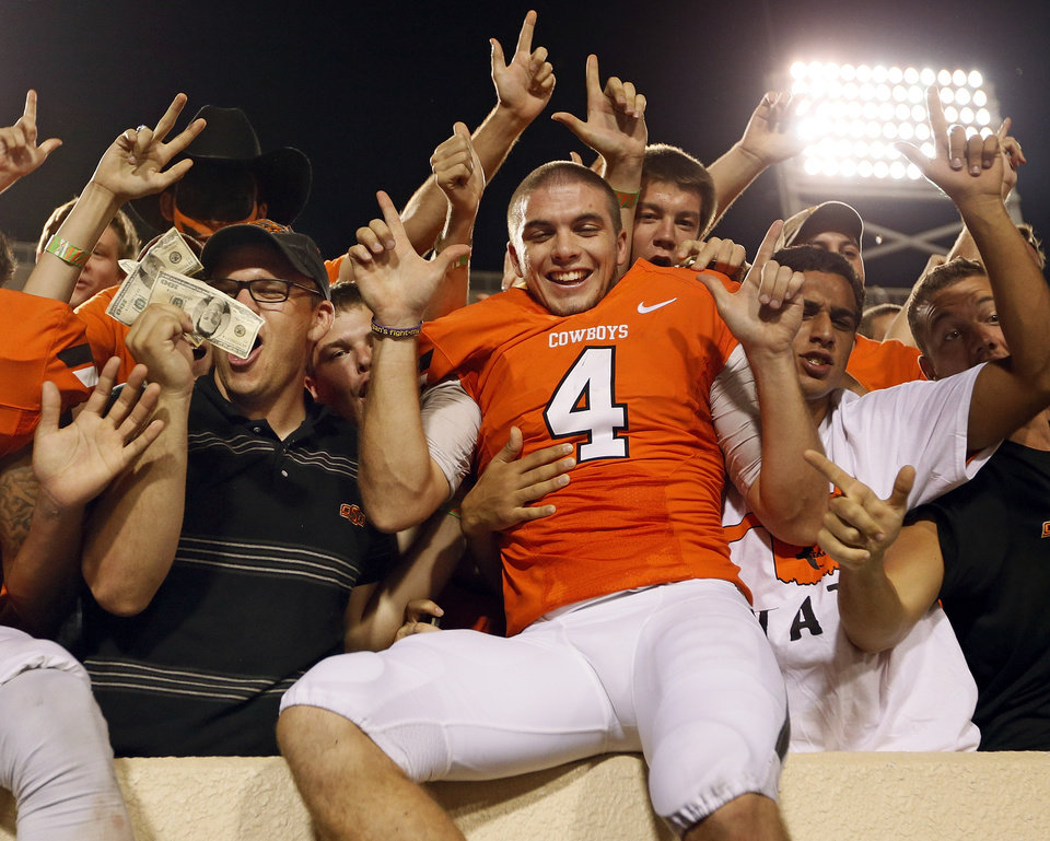 Photo - Oklahoma State's J.W. Walsh (4) celebrates with fans, including one holding fake money, in the stands after a college football game between the Oklahoma State University Cowboys (OSU) and the Lamar University Cardinals at Boone Pickens Stadium in Stillwater, Okla., Saturday, Sept. 14, 2013. The fan with the fake money tried to give it to Walsh, but the quarterback refused to take it. OSU won, 59-3. Photo by Nate Billings, The Oklahoman