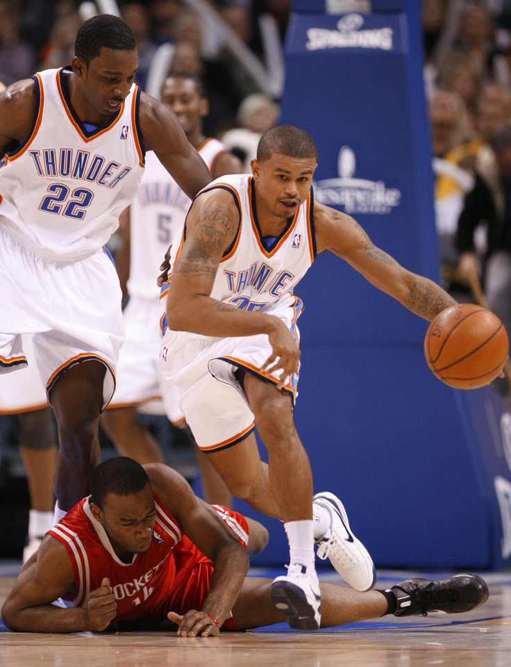 Photo - Earl Watson steals the ball from Carl landry and goes the length of the court for a score in the second half as the Oklahoma City Thunder plays the Houston Rockets at the Ford Center in Oklahoma City, Okla. on Friday, January 9, 2009. 
