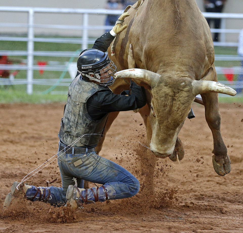 Photo - Dalton Rutledge of Liberal, Kan., falls off during the bull riding competition in the LibertyFest Rodeo in Edmond, Okla., Saturday, June, 22, 2013. Photo by Bryan Terry, The Oklahoman