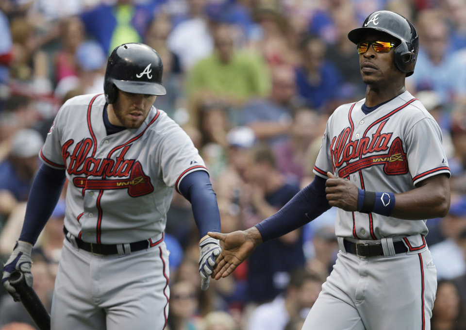 Photo - Atlanta Braves' B.J. Upton, right, celebrates with Freddie Freeman after scoring on a single hit by Andrelton Simmons during the third inning of a baseball game against the Chicago Cubs in Chicago, Saturday, July 12, 2014. (AP Photo/Nam Y. Huh)
