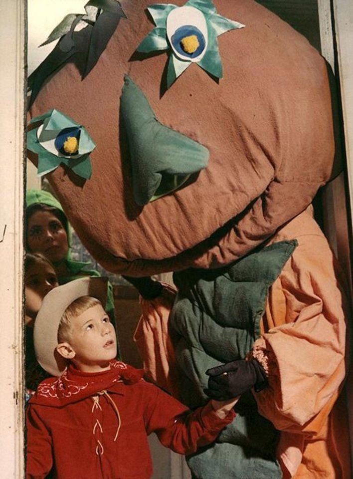 "Photo -  **For Alternate Crop** ""Pufnstuff"" (Mrs. R.J. Riley) welcomes all youngsters to their Haunted House. She holds cowboy Steve Reimer, 6, by the hand. Waiting to enter are Amy Lockard, 9, and Mrs. Harry L. Deupree Jr. who, as one of the guides, is dressed in a pumpkin costume. Photographed on Oct. 25, 1970. Archive photo by unknown photographer."