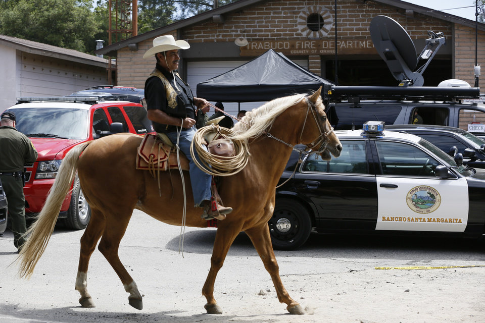 "Rider Francisco Villalobos rides his horse ""Ragalo,"" returns to the Orange County Trabuco Canyon Road command center during the search for missing hiker Kendall Jack, in Rancho Santa Margarita, Calif., Thursday, April 4, 2013.  A sheriff's rescue team, following the sounds of a screaming female voice, found Jack, late Thursday morning clinging to a small rock outcropping along the brush-covered wall. Jack, 18, was found not far from where her 19-year-old hiking companion, Nicolas Cendoya, had been found by a hiker Wednesday night.. (AP Photo/Damian Dovarganes)"
