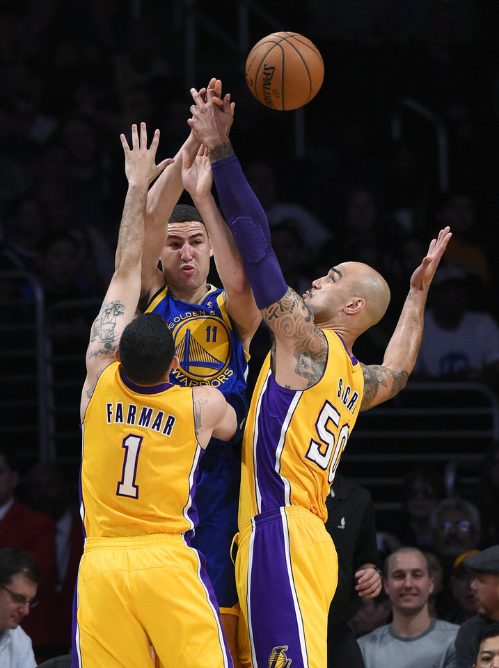 Photo - Golden State Warriors guard Klay Thompson, center, passes the ball as Los Angeles Lakers guard Jordan Farmar, left, and center Robert Sacre defend during the first half of an NBA basketball game, Friday, April 11, 2014, in Los Angeles. (AP Photo/Mark J. Terrill)