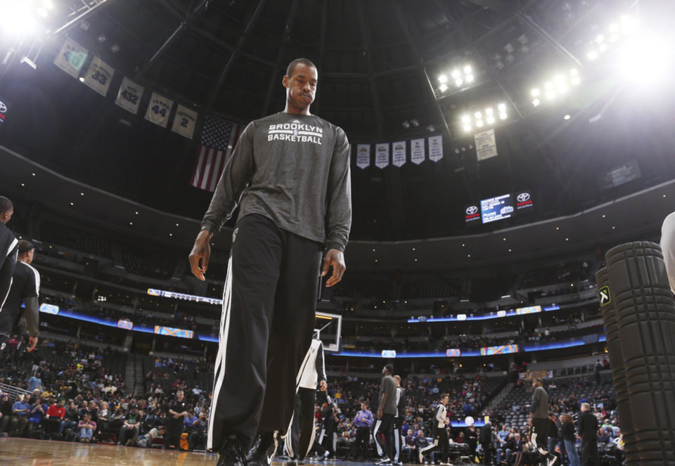 Photo - Brooklyn Nets center Jason Collins warms up before facing the Denver Nuggets in an NBA basketball game in Denver on Thursday, Feb. 27, 2014. (AP Photo/David Zalubowski)