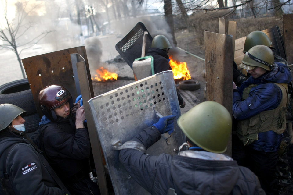 Photo - Anti-government protesters man a barricade at the Independence Square in Kiev, Ukraine, Friday, Feb. 21, 2014. Ukraine's presidency said Friday that it has negotiated a deal intended to end battles between police and protesters that have killed scores and injured hundreds, but European mediators involved in the talks wouldn't confirm a breakthrough. (AP Photo/ Marko Drobnjakovic)