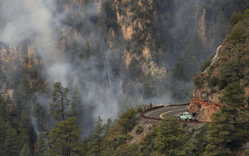 Photo - A truck drives along a road near the the Slide Fire as it burns up Oak Creek Canyon nearby on Friday, May 23, 2014, near Flagstaff, Ariz.  The fire has burned approximately 7,500 acres. (AP Photo/Ross D. Franklin)