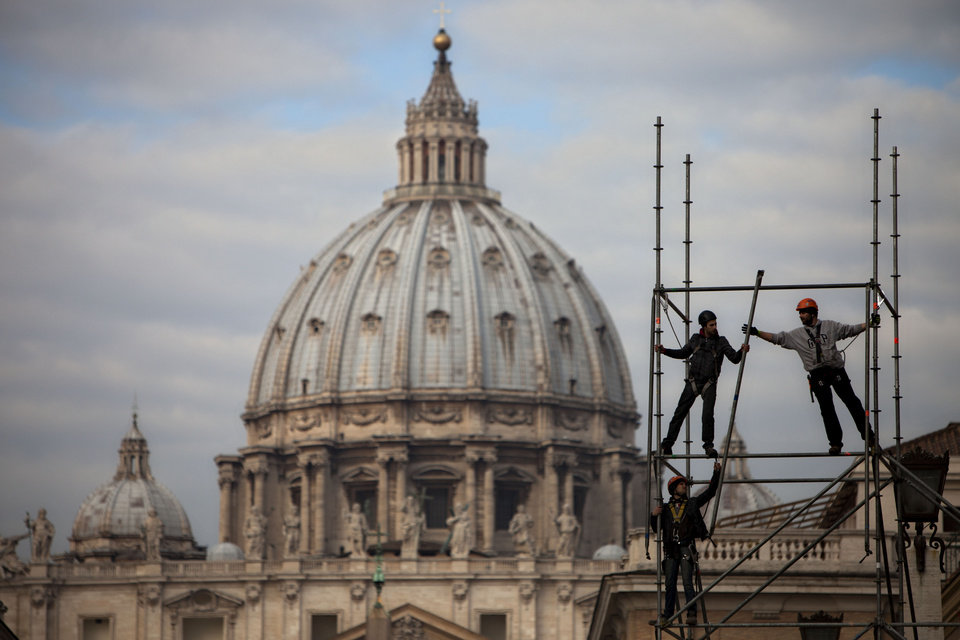 Workers sets up a stage for the media next to St Peter\'s Square ahead of Pope Benedict XVI\'s last public audience Wednesday, at the Vatican, Tuesday, Feb. 26, 2013. Pope Benedict XVI has changed the rules of the conclave that will elect his successor, allowing cardinals to move up the start date if all of them arrive in Rome before the usual 15-day transition between pontificates. Benedict signed a legal document, issued Monday, with some line-by-line changes to the 1996 Vatican law governing the election of a new pope. It is one of his last acts as pope before resigning Thursday. (AP Photo/Oded Balilty)