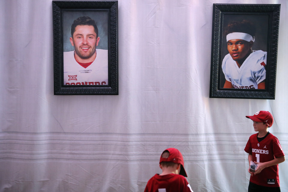 Photo - Braden Looper, 7, left, and his brother Wade, 5, look at paintings of Baker Mayfield and Kyler Murray inside the the Heisman House before a college football game between the University of Oklahoma Sooners (OU) and the West Virginia Mountaineers at Gaylord Family-Oklahoma Memorial Stadium in Norman, Okla, Saturday, Oct. 19, 2019. [Bryan Terry/The Oklahoman]