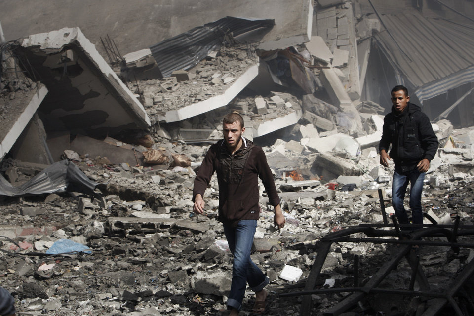 Palestinians walk through the debris after an Israeli air strike on building in Gaza City, Sunday, Nov. 18, 2012. The Israeli military widened its range of targets in the Gaza Strip on Sunday to include the media operations of the Palestinian territory's Hamas rulers, sending its aircraft to attack two buildings used by both Hamas and foreign media outlets. (AP Photo/Adel Hana)