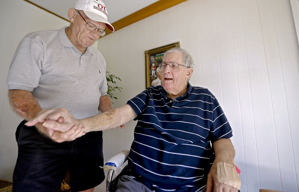 Photo - Former University of Oklahoma football player Brewster Hobby, left, helps his friend and former OU teammate Bob Cornell with his physical therapy at Cornell's home on Thursday, June 12, 2014 in Norman, Okla.  Hobby goes to Cornell's house twice a week to put his former OU teammate through physical therapy after Cornell suffered a 2000 stroke, and suffered a broken hip and hip replacement in 2002. Cornell's progress is slow, but his spirit is strong, thanks in part because of a teammate Hobby who keeps him active.  Photo by Chris Landsberger, The Oklahoman