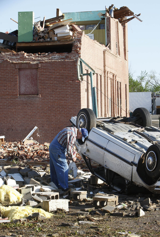Jerome Whittington attempts to salvage belongings through the window of his automobile in Tushka, Okla., Friday, April 15, 2011, following a tornado the night before. (AP Photo/Sue Ogrocki)