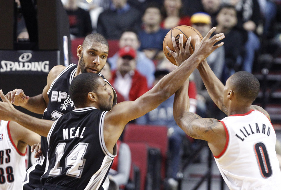 Portland Trail Blazers guard Damian Lillard, right, is double-teamed by the San Antonio Spurs' Gary Neal (14) and Tim Duncan during the first quarter of an NBA basketball game in Portland, Ore., Thursday, Dec. 13, 2012. (AP Photo/Don Ryan)