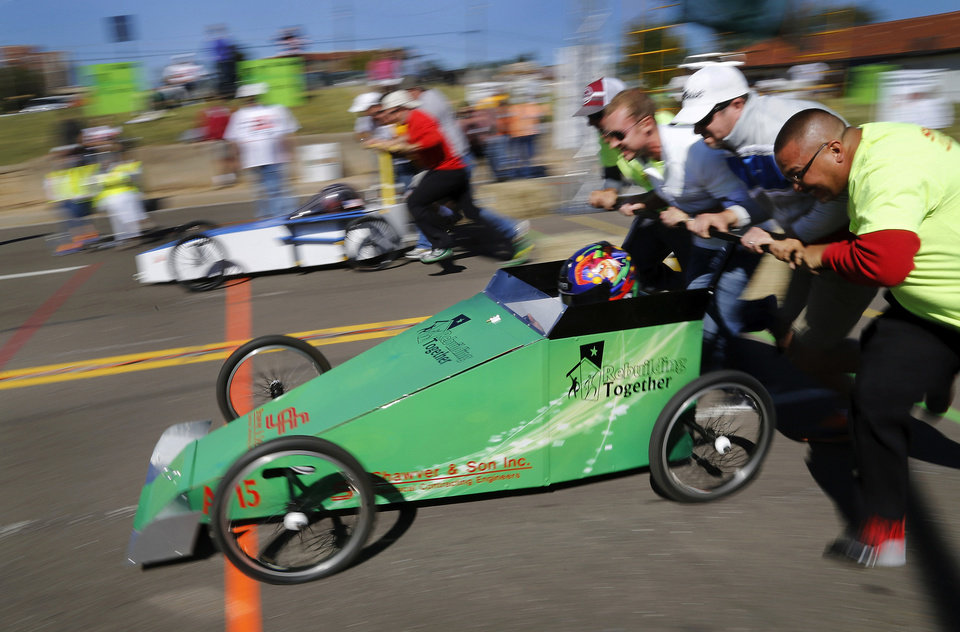 Photo - Crews push their team entries off the starting line.  The car in front, sponsored by Shawver & Son, won the amateur division of the 10th annual Rebuilding Together OKC Construction Derby on Sunday. Twenty-two teams entered non-motorized  vehicles in this year's competition on a course dubbed
