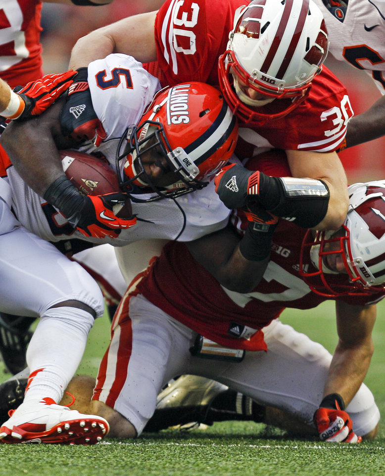 Photo -   Wisconsin linebacker Derek Landisch (30) and defensive back Michael Caputo (7) wrap up Illinois running back Donovonn Young (5) during the second half of an NCAA college football game on Saturday, Oct. 6, 2012, in Madison, Wis. Wisconsin won 31-14. (AP Photo/Andy Manis)