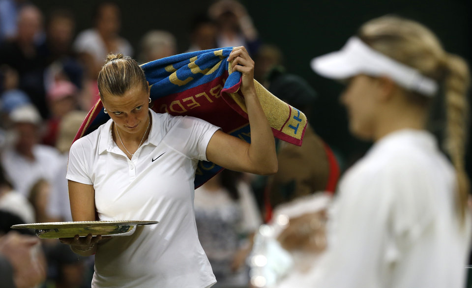 Photo - Petra Kvitova of the Czech Republic, left, looks across at Eugenie Bouchard of Canada during the trophy ceremony after winning the women's singles final match at the All England Lawn Tennis Championships in Wimbledon, London, Saturday, July 5, 2014. (AP Photo/Sang Tan)