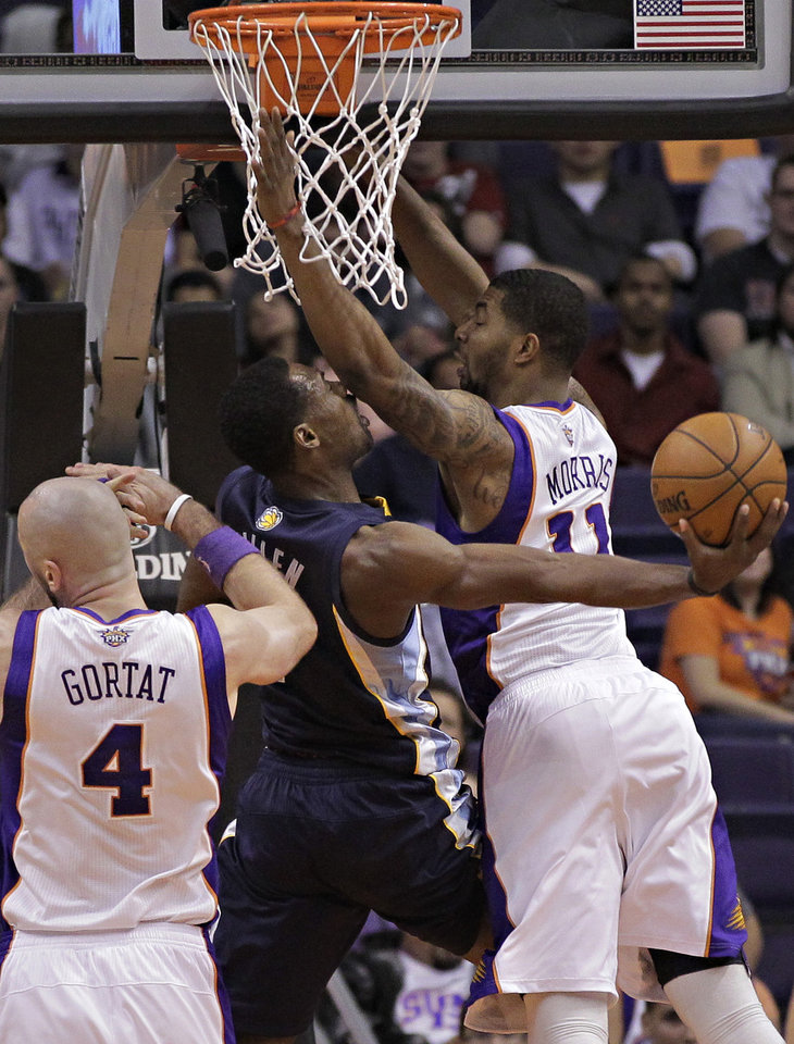 Memphis Grizzlies' Tony Allen, center, scores under pressure from Phoenix Suns' Marcin Gortat, of Poland, 94) and Markieff Morris (11)  during the second half of an NBA basketball game on Wednesday, Dec. 12, 2012, in Phoenix. (AP Photo/Matt York)