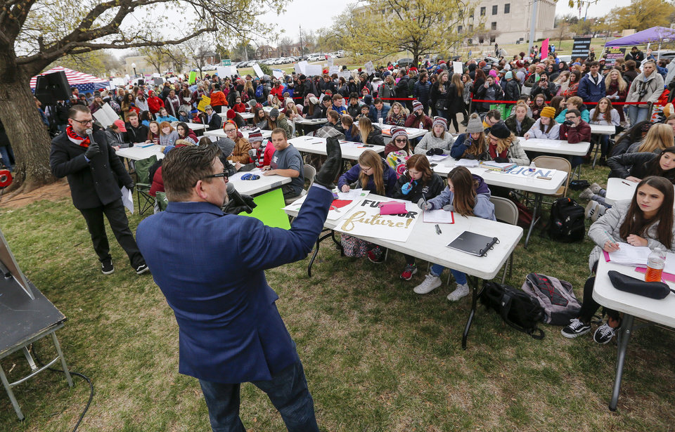 Photo - Edmond Memorial English teachers Brook Bullock, middle, and Regan Killackey, left, lead an AP English class during Edmond Memorial's Class at the Capitol, a teach-in protest, at a walkout and rally by Oklahoma teachers at the state Capitol in Oklahoma City, Monday, April 2, 2018. Photo by Nate Billings, The Oklahoman