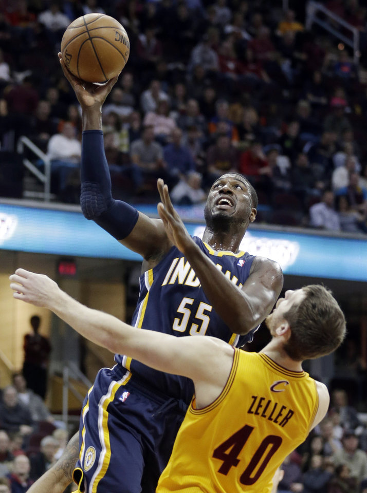Photo - Indiana Pacers' Roy Hibbert (55) jumps to the basket against Cleveland Cavaliers' Tyler Zeller (40) during the first quarter of an NBA basketball game Sunday, Jan. 5, 2014, in Cleveland. (AP Photo/Tony Dejak)