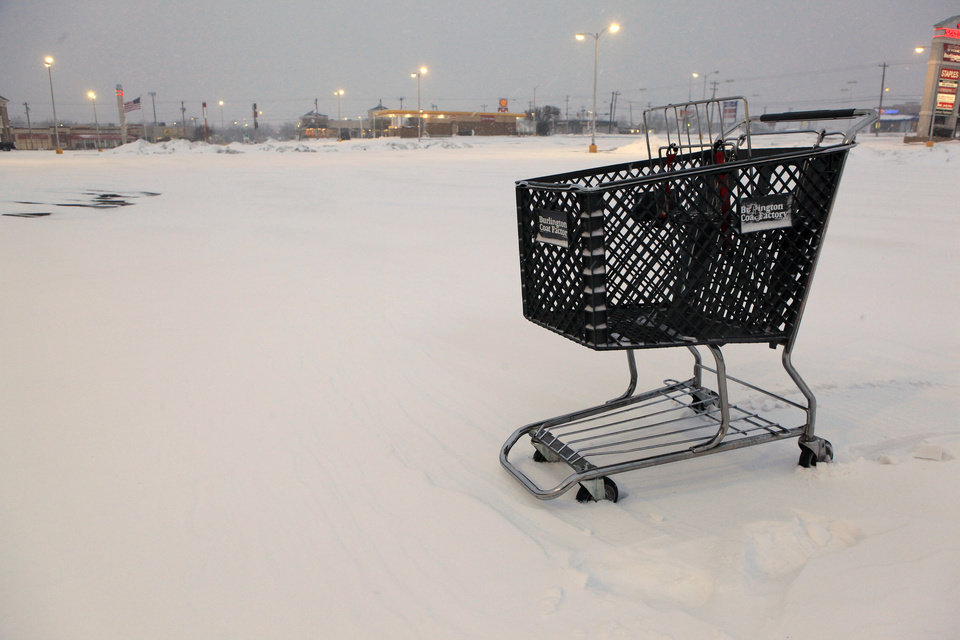 Photo - Shopping cart stuck in the snow in the middle of an empty parking lot  at French Market Mall, NW  63 and May, in Oklahoma City Wednesday, Feb. 9, 2011. Photo by Paul B. Southerland, The Oklahoman