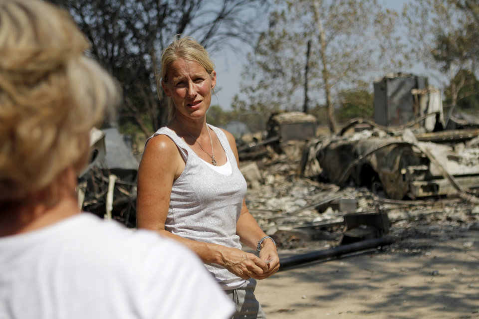 Photo - Steveanne Bielich stands by the remains of her home in northeast Oklahoma City, Wednesday, August 31, 2011. Bielich's home was destroyed by a wildfire on Tuesday, August 30, 2011. Photo by Bryan Terry, The Oklahoman