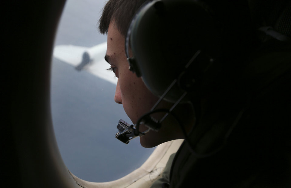 Photo - Sgt. Matthew Falanga on board a Royal Australian Air Force AP-3C Orion, search for the missing Malaysia Airlines flight MH370 in southern Indian Ocean, Australia, Saturday, March 22, 2014.  Frustration grew Saturday over the lack of progress tracking down two objects spotted by satellite that might be Malaysia Airlines Flight 370, with a Malaysian official expressing worry that the search area will have to be widened if no trace of the plane is found. (AP Photo/Rob Griffith, Pool)