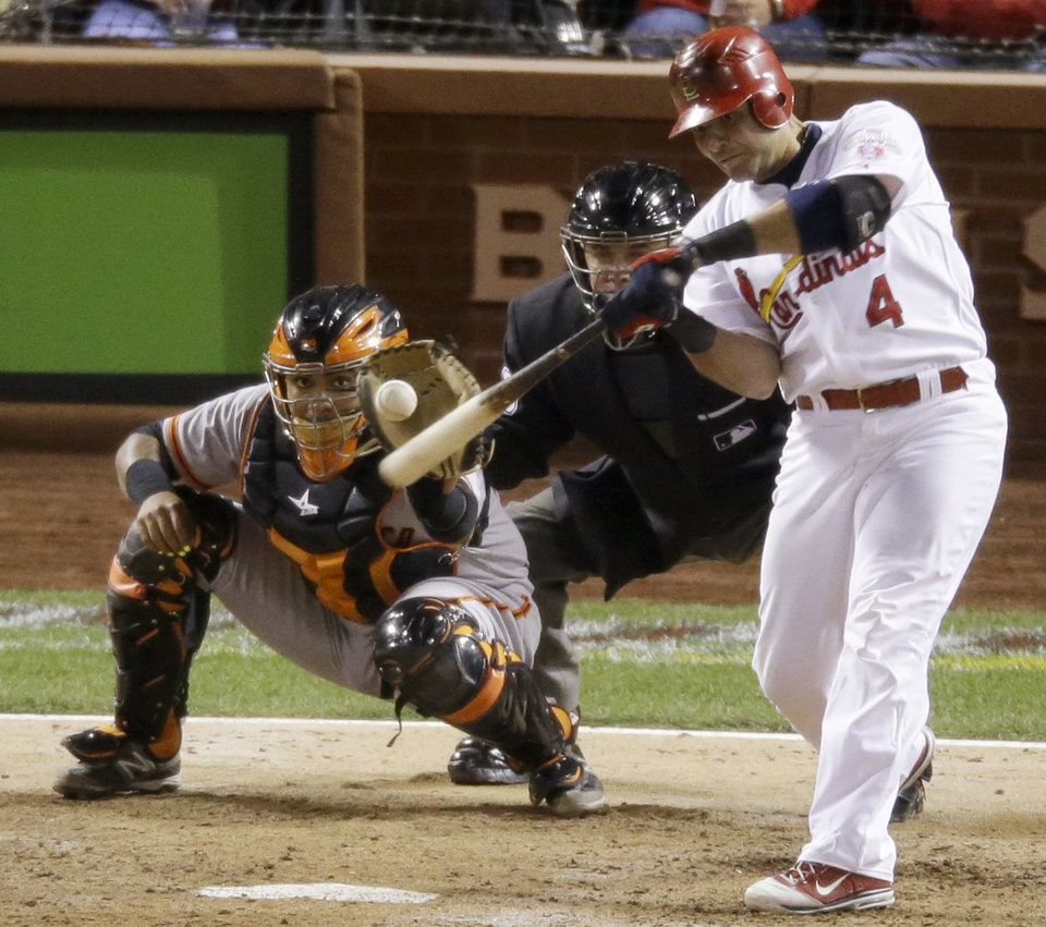 Photo -   St. Louis Cardinals' Yadier Molina hits a run-scoring double during the seventh inning of Game 4 of baseball's National League championship series against the San Francisco Giants Thursday, Oct. 18, 2012, in St. Louis. (AP Photo/Mark Humphrey)