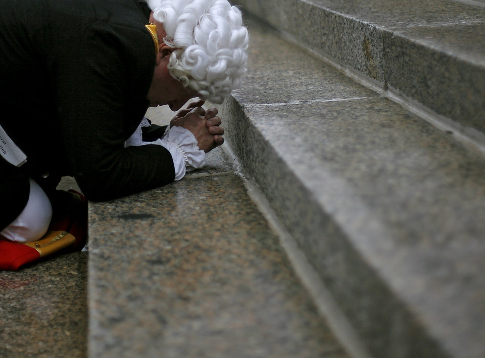 Photo - Dressed in the style of the Founding Fathers, Buddy Ray kneels to pray on the north side steps of the Oklahoma State Capitol at the end of a Health Care Reform rally in Oklahoma City on Sunday, Sept. 13, 2009.  By John Clanton, The Oklahoman
