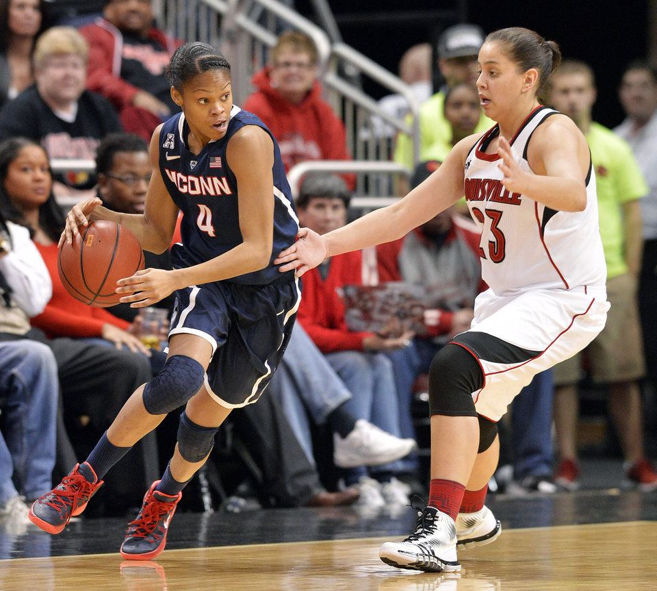 Photo - Connecticut Moriah Jefferson, left, attempts to drive around the defense of Louisville's Shoni Schimmel during the first half of an NCAA college basketball game, Monday, March 3, 2014, in Louisville, Ky. (AP Photo/Timothy D. Easley)