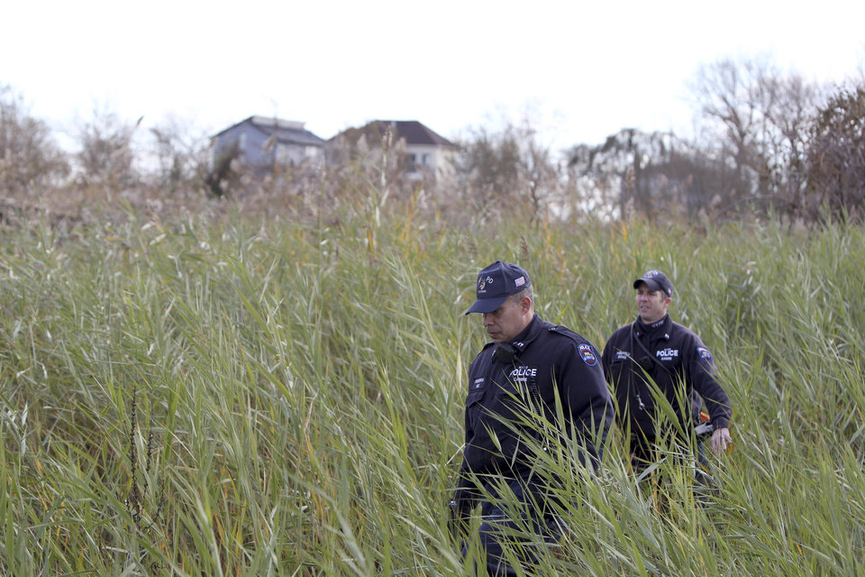 Police officers wearing wet suits leave a site where the body of a 2-year-old child killed during Superstorm Sandy was discovered in Staten Island, New York, Thursday, Nov. 1, 2012. Brandon Moore, 2, and Connor Moore, 4, were swiped into swirling waters as their mother tried to escape her SUV on Monday amid rushing waters that caused the vehicle to stall during Superstorm Sandy. Police said the mother, Glenda Moore, was going to her sister's home in Brooklyn when she tried to flee the vehicle with the boys, only to have the force of the rising water and the relentless cadence of pounding waves rip the boy's small arms from her. (AP Photo/Seth Wenig)