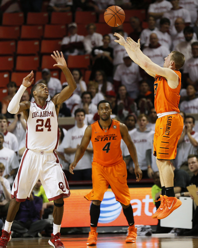 Photo - Oklahoma State's Phil Forte (13) makes a three-point shot over Oklahoma's Buddy Hield (24) as Oklahoma State's Brian Williams (4) looks on late in the second half during the NCAA men's Bedlam basketball game between the Oklahoma State Cowboys (OSU) and the Oklahoma Sooners (OU) at Lloyd Noble Center in Norman, Okla., Monday, Jan. 27, 2014. OU won, 88-76. Photo by Nate Billings, The Oklahoman