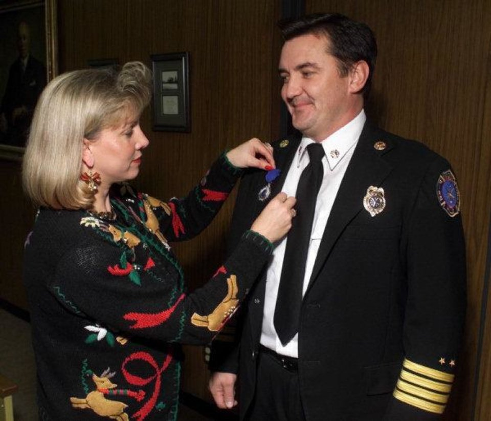 Photo - In a Dec. 14, 1999 photo, Becky Bryan pins a firefighter lifesaving medal on her husband, Nichols Hills Fire Chief Keith Bryan. Keith Bryan was shot Tuesday nightv at his home in Mustang and died later at a local hospital.  STEVE GOOCH - AP