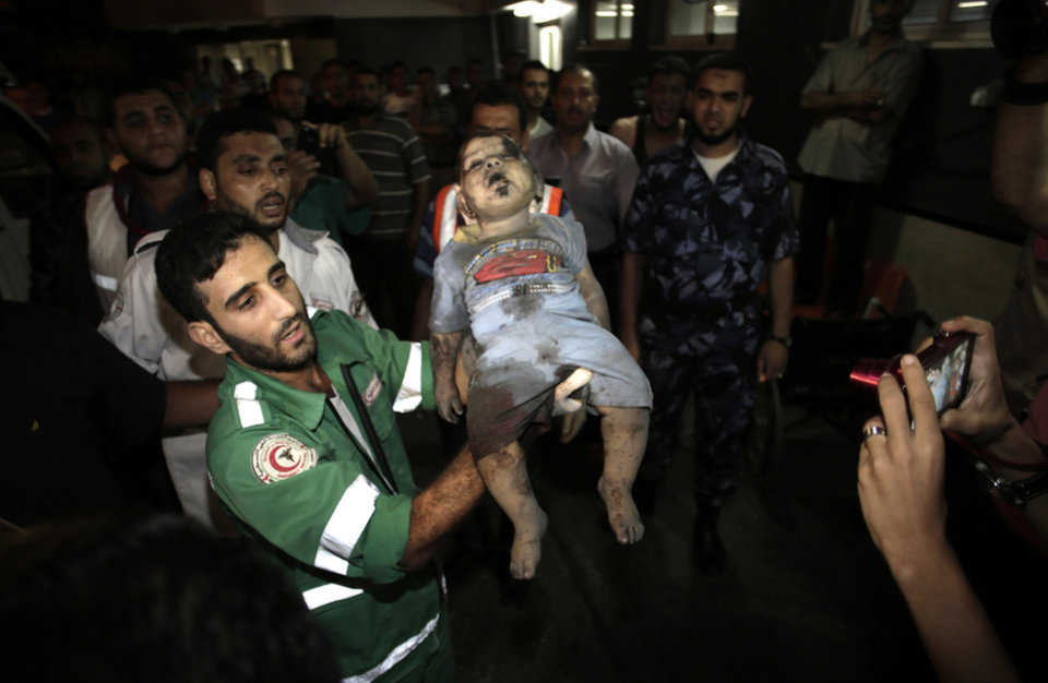 Photo - EDS NOTE: GRAPHIC CONTENT - A Palestinian medic carries the body of a baby girl as she is brought to the Shifa hospital following Israeli strikes which hit Gaza City, Tuesday, Aug. 19, 2014. Israel resumed its campaign of airstrikes in Gaza on Tuesday in response to a barrage of Palestinian rocket fire that shattered a truce. The sudden burst of fighting has threatened to derail an Egyptian effort to end a monthlong war between Israel and Hamas militants in Gaza. (AP Photo/Khalil Hamra)