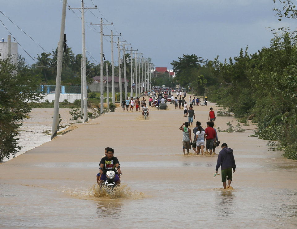Photo - Residents wade through floodwaters brought about by Typhoon Koppu at Zaragosa township, Nueva Ecija provinc,e north of Manila, Philippines Monday, Oct. 19, 2015. Slow-moving Typhoon Koppu blew ashore with fierce wind in the northeastern Philippines early Sunday, toppling trees and knocking out power and communications and forcing the evacuation of thousands of villagers.(AP Photo/Bullit Marquez)