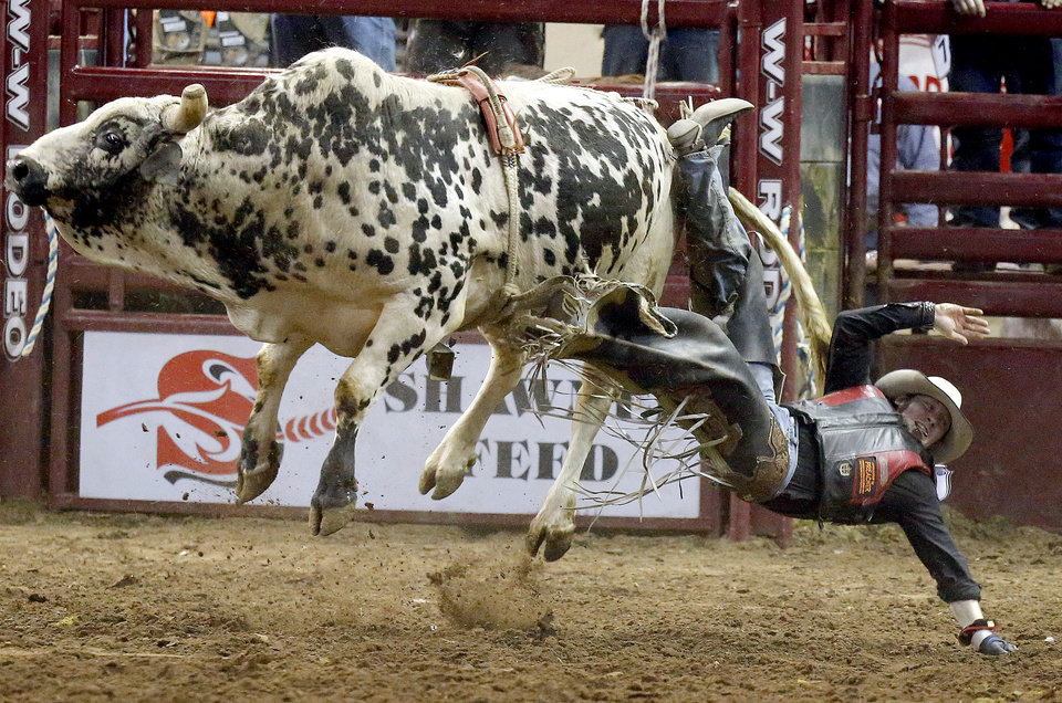 Dustin McMullen of Ingersoll, Ontario, Canada, falls off a bull during the bull riding event at the International Finals Rodeo at the State Fair Arena in Oklahoma City,  Saturday,Jan. 19, 2013. Photo by Sarah Phipps, The Oklahoman