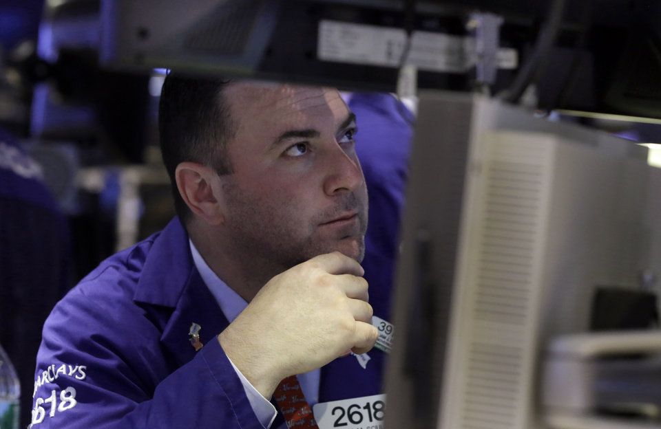 Photo - Specialist James Sciulli works at his post on the floor of the New York Stock Exchange Monday, June 23, 2014. Stocks are edging lower in early trading after indexed closed last week at record highs. (AP Photo/Richard Drew)