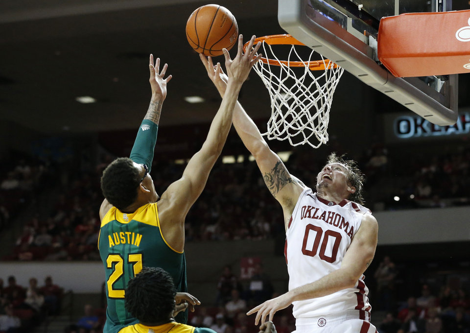 Photo - Oklahoma forward Ryan Spangler (00) and Baylor center Isaiah Austin (21) reach for a rebound in the second half of an NCAA college basketball game in Norman, Okla., Saturday, Feb. 8, 2014. Oklahoma won 88-72. (AP Photo/Sue Ogrocki)
