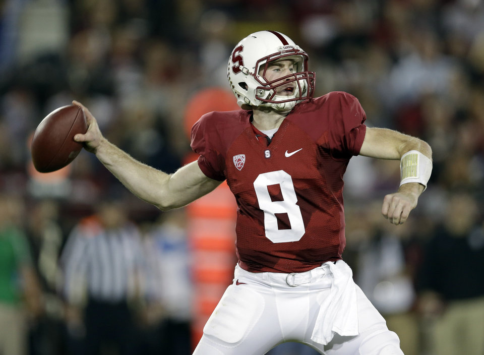 Photo - Stanford quarterback Kevin Hogan (8) throws against Notre Dame during the first half of an NCAA college football game on Saturday, Nov. 30, 2013, in Stanford, Calif. (AP Photo/Marcio Jose Sanchez)
