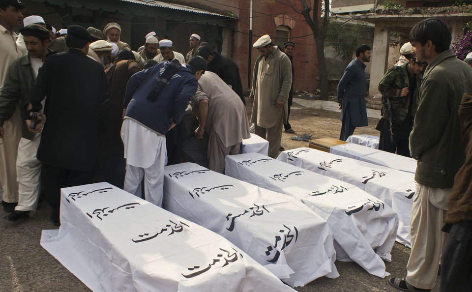 Photo - Pakistanis stand near coffins of people killed from a bomb blast in the Pakistani tribal area of Khyber, Monday, Dec. 17, 2012. A car bomb exploded outside the women's waiting area of a government office in Pakistan's troubled northwest tribal region, killing many  people and wounding others, government officials said. (AP Photo/Qazi Rauf)