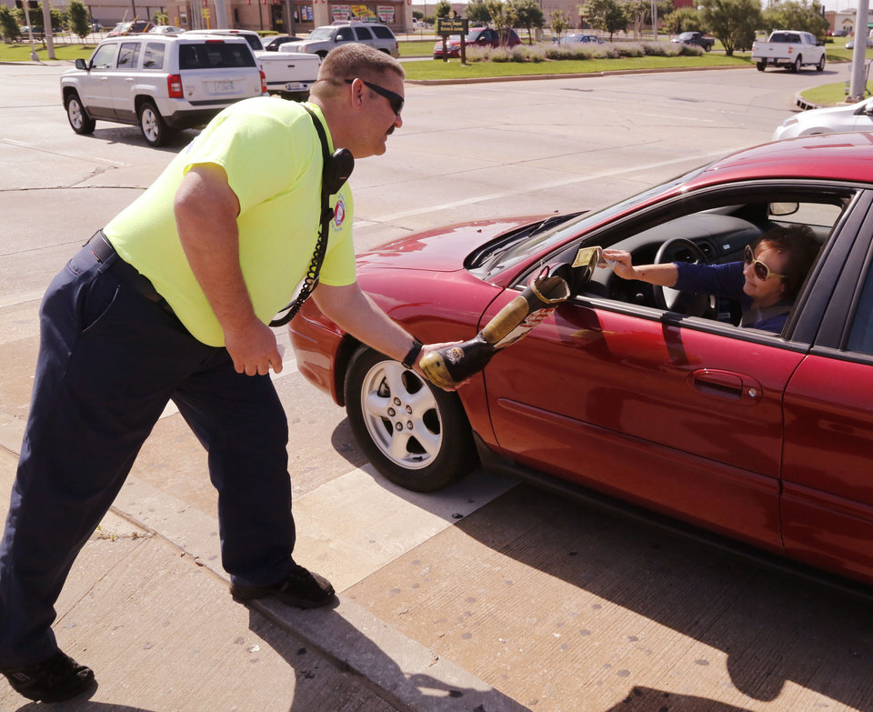 Photo - OKC Station 1 firefighter Clint Greenwood leans and stretches to collect for MD at the intersection of Pennsylvania and Memorial Rd. in Oklahoma City, Okla. Saturday, May 28, 2016. Due to the new city ordinance, firefighters are not allowed to step off of a curb, which is limiting their ability to collect funds. Photo by Paul Hellstern, The Oklahoman