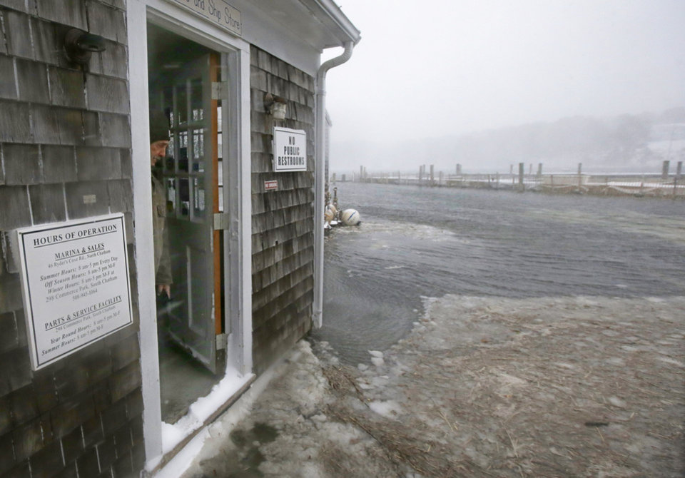 Photo - Alan Cohen, owner of the Ryder's Cove Marina watches rising water and slush approach his office door near a waxing high tide in Chatham, Mass., Wednesday morning, March 26, 2014. A blizzard warning is in effect for Cape Cod, Martha's Vineyard and Nantucket as forecasters warned of wind gusts as high as 70 mph with near-zero visibility at times. (AP Photo/Stephan Savoia)