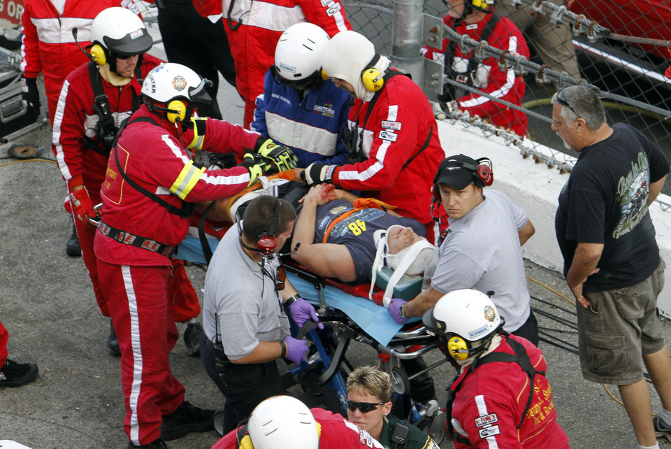 An injured spectator is treated after a crash at the conclusion of the NASCAR Nationwide Series auto race Saturday, Feb. 23, 2013, at Daytona International Speedway in Daytona Beach, Fla. Driver Kyle Larson's car hit the safety fence sending car parts and other debris flying into the stands.(AP Photo/David Graham)