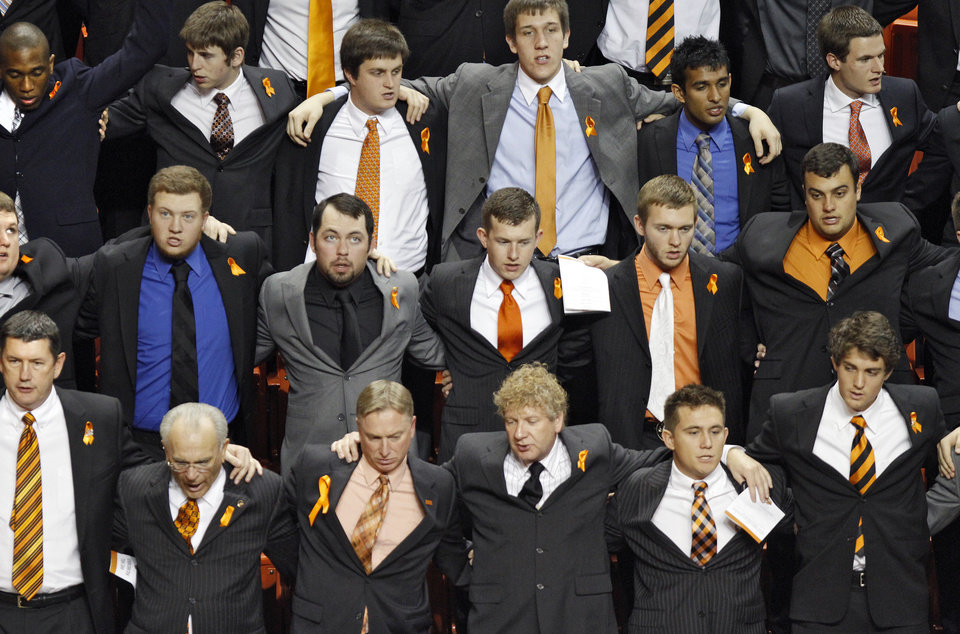 Photo - Members of the Oklahoma State family join arm in arm to sing the alma mater during the memorial service for Oklahoma State head basketball coach Kurt Budke and assistant coach Miranda Serna at Gallagher-Iba Arena on Monday, Nov. 21, 2011 in Stillwater, Okla. The two were killed in a plane crash along with former state senator Olin Branstetter and his wife Paula while on a recruiting trip in central Arkansas last Thursday. Photo by Chris Landsberger, The Oklahoman