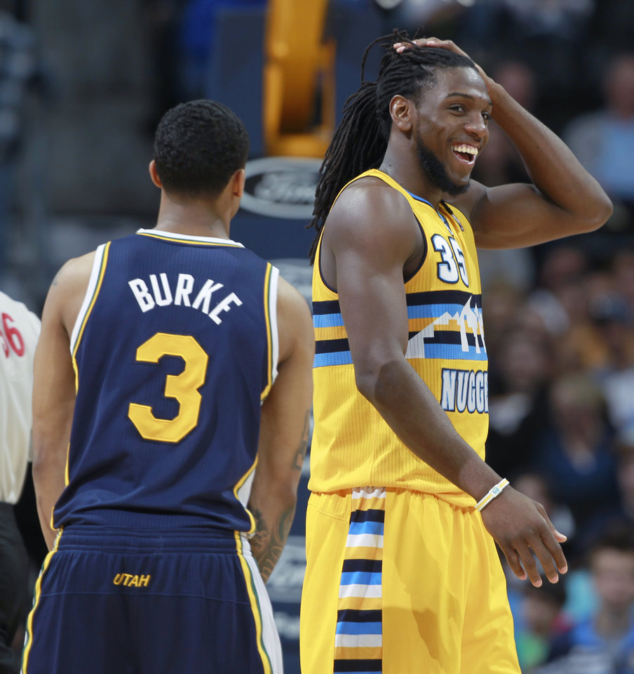 Photo - Denver Nuggets forward Kenneth Faried, right, smiles at teammates as he passes by Utah Jazz guard Trey Burke on the way to the foul line late in the fourth quarter of the Nuggets' 101-94 victory in an NBA basketball game in Denver on Saturday, April 12, 2014. Faried scored 24 points and collected 21 rebounds to notch the first 20-20 game of his career. (AP Photo/David Zalubowski)
