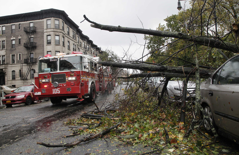 Photo -   A fire truck passes a tree that has fallen across parked cars in the Brooklyn borough of New York the morning after superstorm Sandy struck, Tuesday, Oct. 30, 2012. A record storm surge that was higher than predicted along with high winds damaged the electrical system and plunged millions of people into darkness. Utilities say it could be up to a week before power is fully restored. (AP Photo/Mark Lennihan)