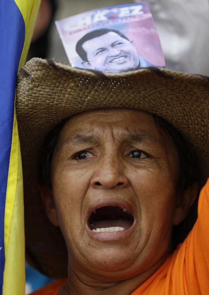 A supporter of Venezuela's President Hugo Chavez wears a hat decorated with a photograph of him as she shouts outside the National Assembly in Caracas, Venezuela, Saturday, Jan. 5, 2013. The Assembly voted to retain Diosdado Cabello as legislative leader, signaling the ruling party's desire to stress unity and continuity amid growing signs the government plans to postpone Chavez's inauguration for a new term while he fights a severe respiratory infection nearly a month after cancer surgery in Cuba.  (AP Photo/Ariana Cubillos)